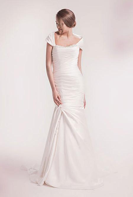 Vòng một của cô dâu sẽ được nâng đỡ và phần bắp tay che đi nhờ vải phủ vai.