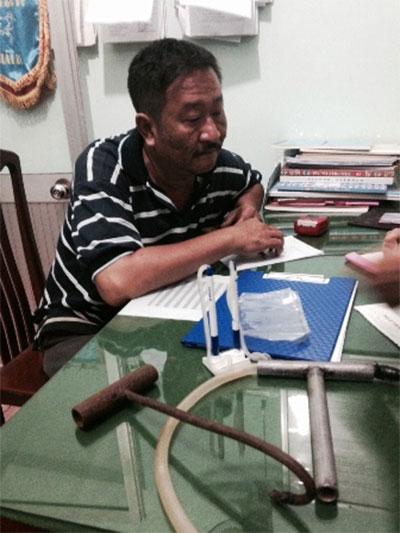 Ông Trần Anh Tấn và một số dụng cụ bơm nước vào heo.